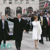 Emerging from their armored limousine, President George W. Bush and first lady Laura Bush wave to well wishers as they prepare to travel 1.7-miles along the inaugural parade route.